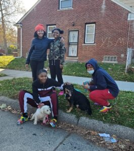 Teenagers posing with Detroit Pit Crew Dog Rescue Animals.